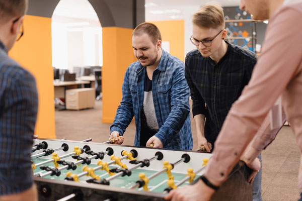 young-office-workers-playing-table-soccer